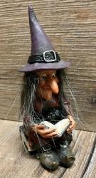 Figur - Lustige Hexe liest - sitzt auf Büchern - mit Buch